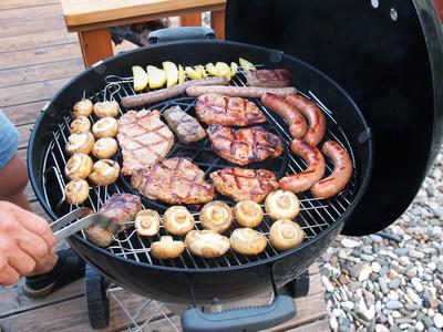 Voll bestückter Gas Kugelgrill mit Fleisch, Wurst und Gemüse