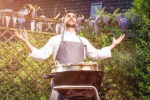 Glücklicher Grillmeister bei der Arbeit vor seinem Gas Kugelgrill